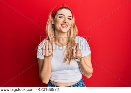 Young caucasian woman wearing casual white t shirt doing money gesture with hands, asking for salary payment, millionaire business