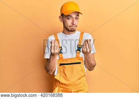 Hispanic young man wearing handyman uniform doing money gesture with hands, asking for salary payment, millionaire business