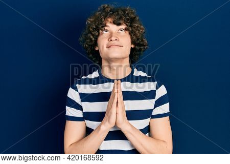 Handsome young man wearing casual striped t shirt begging and praying with hands together with hope expression on face very emotional and worried. begging.