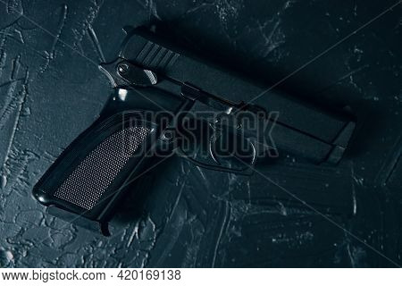 Gun On Green Concrete Texture Table. Ammunition Of Law Enforcement Agencies. Firearm For Defense Or