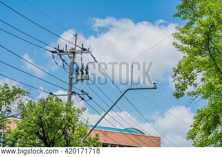 Closed Circuit Camera Mounted On Metal Pole Beside Power Lines With Cloudy Blue Sky In Background.