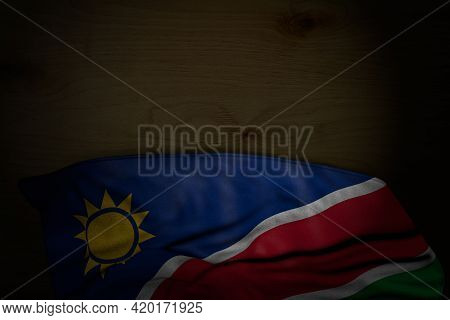 Beautiful Dark Illustration Of Namibia Flag With Big Folds On Dark Wood With Free Space For Content
