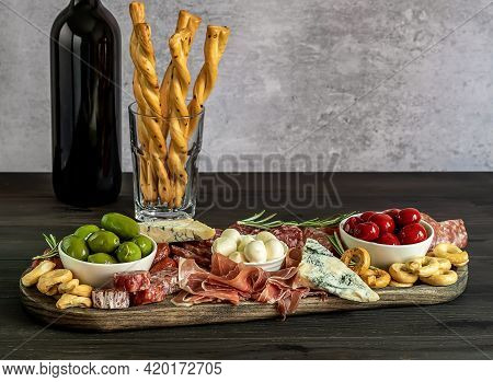 Italian Antipasti Or Charcuterie Board With Bottle Of Wine For A Holiday Entertainment. Assortments