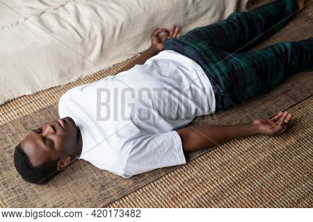 Young Black Man Lying In Dead Body Exercise Or Corpse Pose With His Eyes Closed, Savasana Pose
