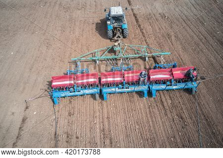 Sowing Campaign. The Tractor Sows The Field With Grain. There Are Two Seeders Sitting On The Planter