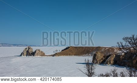 In The Vastness Of The Frozen Lake, An Unusual Two-headed Rock, Devoid Of Vegetation, Rises. Steep R