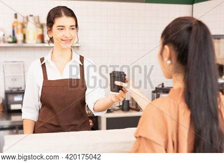 Beautiful Caucasian Barista Woman Gives Takeaway Coffee Cup To The Customer And Looking To Customer