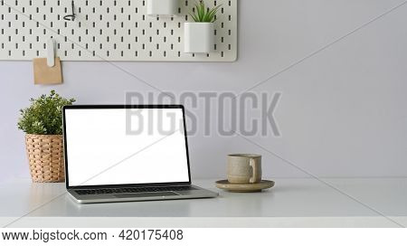Photo Of White Blank Screen Computer Laptop Putting On White Working Desk That Surrounded By Coffee