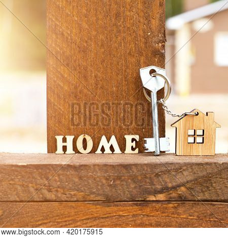 Keychain Of Wooden Figure House On Fence With Key And Inscription In English Letters