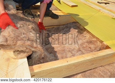 Roofing Insulation. A Roofing Contractor Is Installing Mineral Wool, Glass Wool Insulation Between T