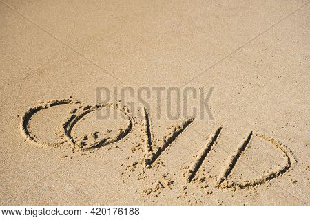 Covid Written On The Sand Of A Beach With Wave Washing The Word, Erasing Or Canceling It During Coro