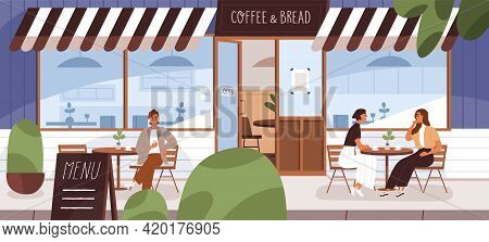 People Drinking Coffee On Cafe Terrace In Summer. City Bakery Building With Street Tables And Chairs