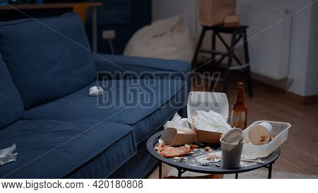 Leftover Of Pizza, Empty Beer Bottles And Napkins On Misery Table And Floor