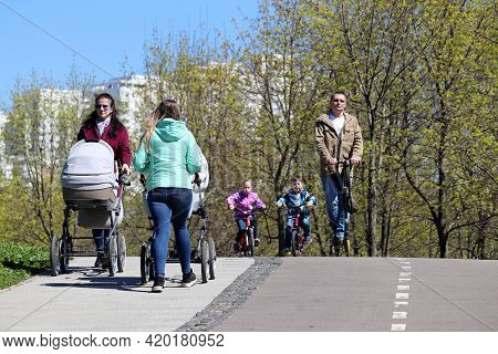 Moscow, Russia - May 2021: Women Walking With Prams In Park On Background Of Children Riding On Bicy