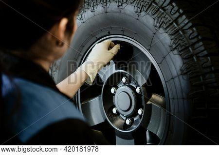 Mechanic opening valve stem on a tire
