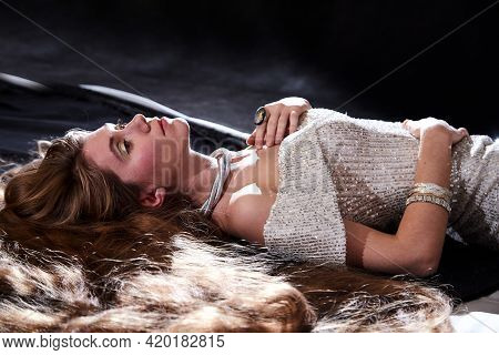 Young Attractive Girl With Long Blonde Hair And Beautiful Dress Posing Lying On The Floor In Studio