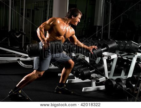 poster of very power athletic guy execute traction with dumbbells exercise on broadest muscle of back in sport hall