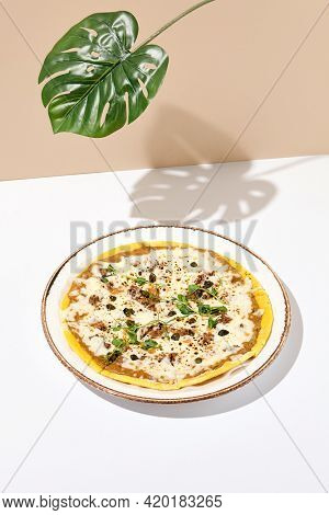 Modern minimal photo of oven pizza with tuna and capers, great design for any purposes. Pizza poster. White table with beige wall in sunshine with palm leaf shadow. Pizza summer day concept