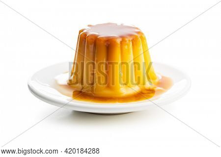Sweet vanilla pudding. Sweet dessert with caramel topping isolated on white background.