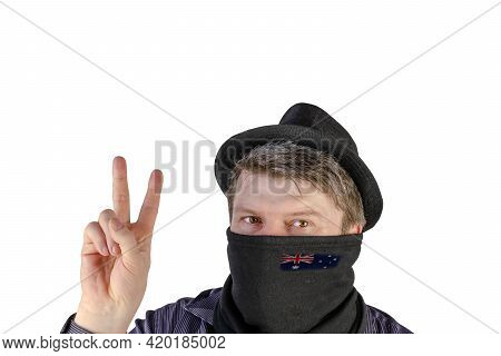 Adult Man In A Black Hat With Small Fields And A Scarf Over His Face Shows A Victory Gesture. Scarf