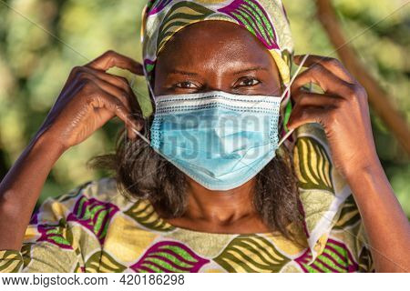 African middle aged woman, female in Africa, wearing traditional clothes and putting on face mask in Coronavirus COVID-19 pandemic