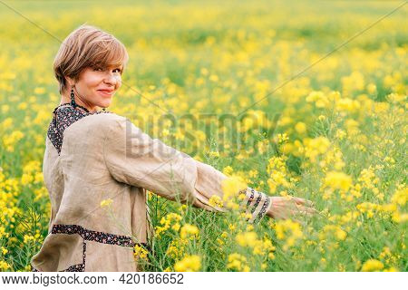 Blond Woman On Floral Hippie Dress. She Is On A Rape Flower Field And Extends Her Arms While Looking
