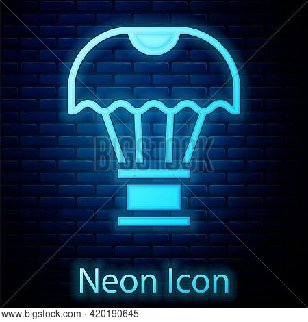 Glowing Neon Box Flying On Parachute Icon Isolated On Brick Wall Background. Parcel With Parachute F