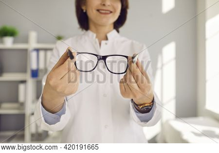 Close Up Of Glasses In The Hands Of A Female Optometrist In A Clinic Or Optics Store.