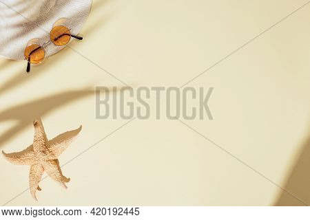 Summer Minimal Background With Sunhat, Colored Sunglasses, Starfish On Sandy Color Background With D