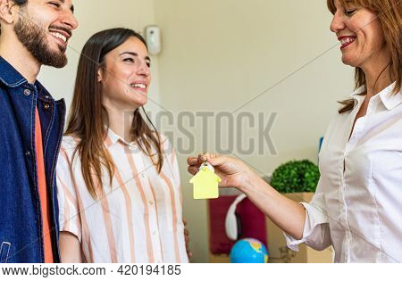 Real Estate Agent Handing Over The Key To The Happy Couple. Buy, Rent And Owners Concept.
