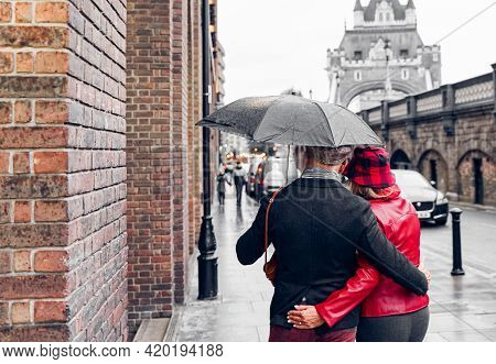 Couple Walking In The Rain Under A Beautiful Tower Bridge Of London. Retired Couple Traveling Around