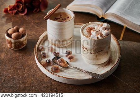 Two Cups Of Coffee With Foam And Marshmallow And Sublimated Raspberries With Cinnamon On Light Plate