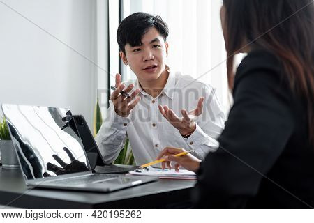 Young Asian Male Mentor Coach Worker Talking To Female Coworker Teaching Intern Having Business Conv