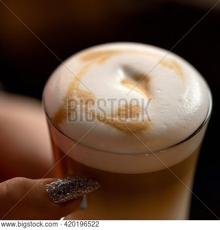 Glass Of Latte Coffee With Froth In Female Hand. Close Up Shot, Top View. Soft Focus.