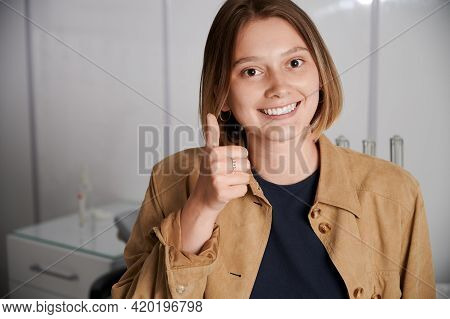 Portrait Of Pretty Brunette Giving Thumbs Up At Dentist Office. Young Girl With Beautiful Healthy Sm