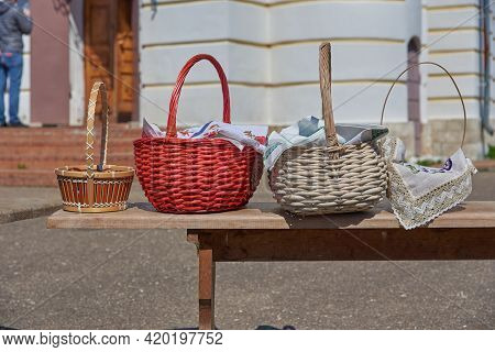 Wicker Baskets With Eggs And Cakes Stand On A Bench In Front Of The Church On The Feast Of Bright Ea