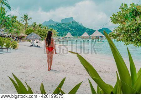 Beach travel vacation luxury hotel in Bora Bora island, Tahiti, French Polynesia. Bikini model walking relaxing on beach, view from behind. Natural beauty nature landscape.