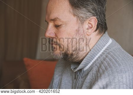 Middle-aged Man Alone At Home And Looking Down And Depressed