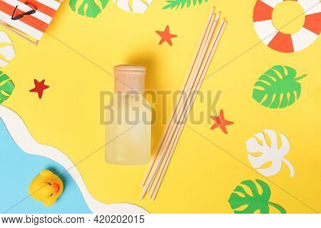 Fragrances For The Home. Bottle Of Natural Fragrances With Bamboo Sticks On Summer Yellow Background