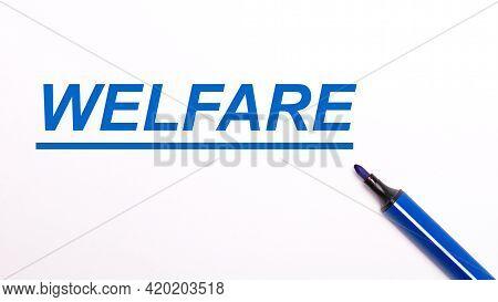 On A Light Background, An Open Blue Felt-tip Pen And The Text Welfare