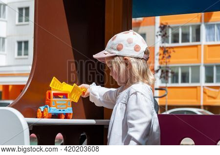 Girl Playing With Toy Outdoor. Kid Playing With Tiny Car On The Playground. Child Girl Toddler Playi
