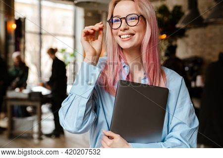 Young beautiful woman with pink hair smiling and holding laptop in cafe