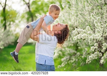 Mom Plays In The Spring Garden With A Young Son, Throws The Child Up.