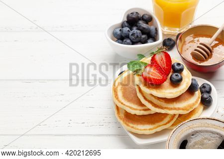 Healthy breakfast with pancakes. Homemade american pancakes with berries and honey. With copy space