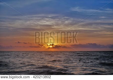 Dawn Over The Caribbean Sea. The Sun Shines Through The Gap In The Clouds. The Blue Sky Is Backlit W