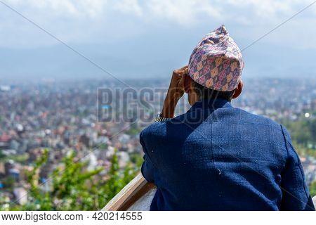 KATHMANDU, NEPAL - CIRCA MARCH 2015: Nepali man wearing a topi contemplates Kathmandu city from Swayambhunath.
