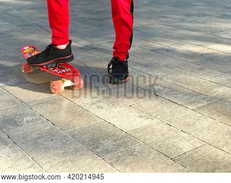 Lviv Ukraine - 05 10 2021: Fragment Of The Legs Of A Boy In Red Sportswear On A Skateboard On A City