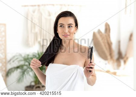 Happy European Young Pretty Brunette Female In Towel With Comb Enjoys Silky, Healthy, Perfect, Long