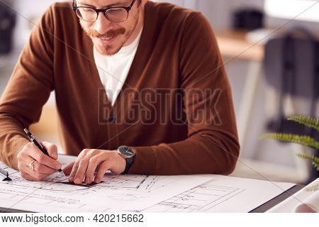 Close Up Of Male Architect At Desk In Office Amending Building Plans