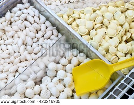 Frozen Dumplings Sold By Weight In A Refrigerator Container On A Store Counter. Frozen Food Sales